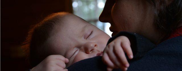 Enfant qui dort dans les bras de sa maman.